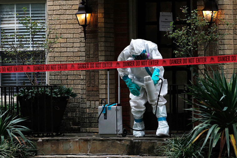 A man dressed in protective hazmat clothing treats the front porch of an apartment where a second person diagnosed with the Ebola virus resides on Oct. 12, 2014 in Dallas, Texas. (Photo by Mike Stone/Getty)