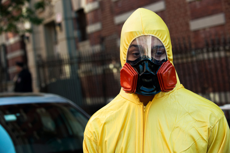 A young man, dressed in a biohazard costume, stands on the corner of 546 West 147th Street on October 25, 2014 in New York City.