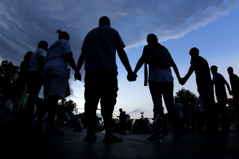 In this Aug. 20, 2014 fill photo people stand in prayer after march in Ferguson, Mo., to protest the shooting of Michael Brown. (Photo by Charlie Riedel/AP)