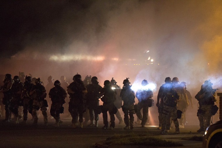 Riot police clear demonstrators from a street in Ferguson, Mo., Aug. 13, 2014. (Photo by Mario Anzuoni/Reuters)