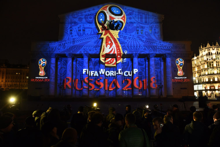 People watch as the facade of the historical Bolshoi Theatre is illuminated with the official emblem of the 2018 FIFA World Cup to be held in Russia in central Moscow on late Oct. 28, 2014. (Photo by Kirill Kudryavtsev/AFP/Getty)