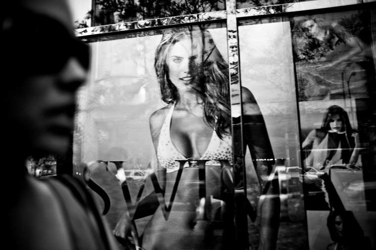 A window reflection of a woman passing by the Victoria's Secret store in Chicago.
