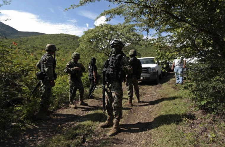 Soldiers guard an area where a mass grave was found, in Colonia las Parotas on the outskirts of Iguala, in Guerrero