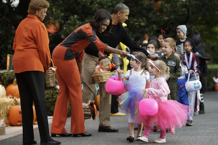 President Barack Obama, first lady Michelle Obama and her mother Marian Robinson, far left, hand out Halloween treats to 'trick-or-treaters' on the South Lawn of the White House in Washington, D.C., on Oct. 31, 2013. (Photo by Pablo Martinez Monsivais/AP)
