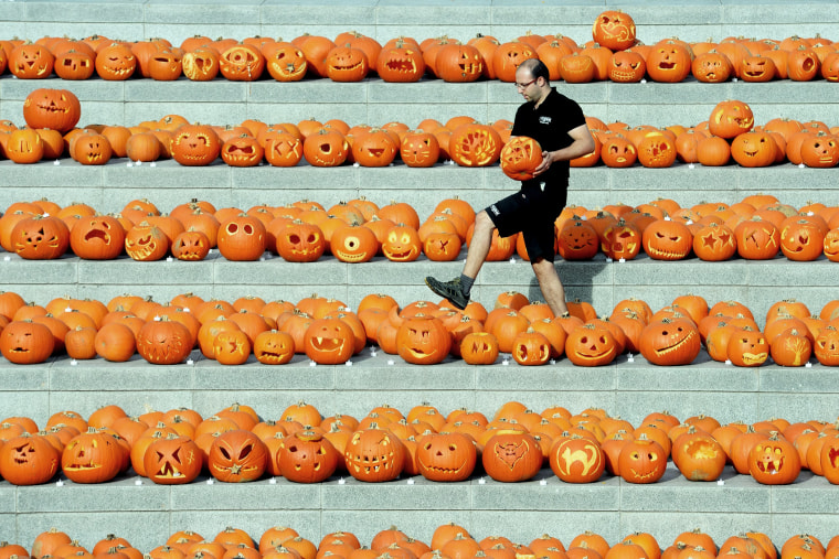 A worker carries a carved pumpkin amongst some of the 3000 pumpkins in Granary square nest to Regents canal in central London, England, Oct. 31, 2014.