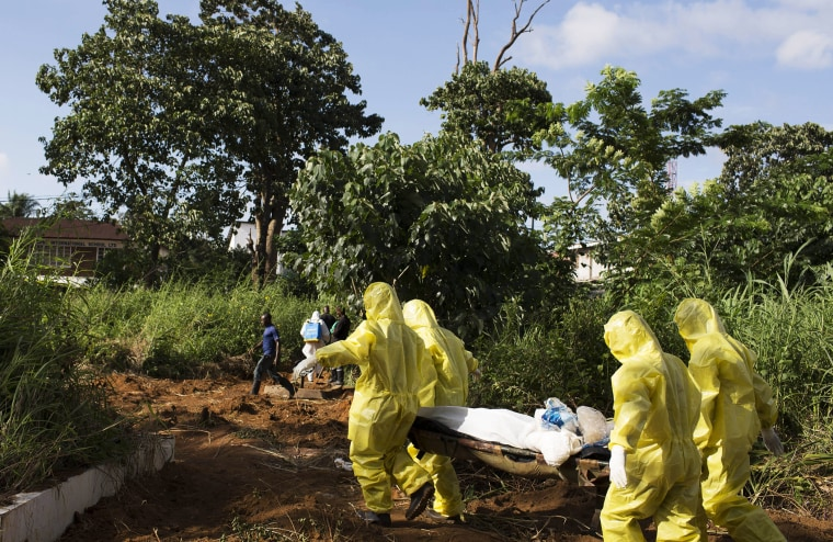 A burial team wearing protective clothing prepared the body of a person suspected to have died of the Ebola virus for interment, in Freetown, Sierra Leone, on Sept. 28, 2014.