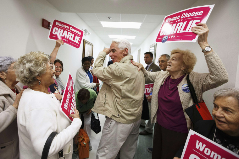 Former Florida Governor and Democratic gubernatorial candidate Charlie Crist (C) heads out of the Mid-County Senior Center, during a four-city bus campaign tour in Lake Worth, Fla. on Nov. 3, 2014.