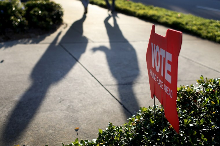 Voters cast shadows as they walk to the polling station past a sign pointing the way to The Coliseum where a polling station is setup on Nov. 4, 2014 in St Petersburg, Fla.