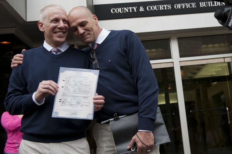 Terrence Hall (L) and Christopher DeCaria (R) display their marriage license to the media outside of the Mecklenburg County Register of Deeds office in Charlotte, North Carolina, on Oct. 13, 2014.
