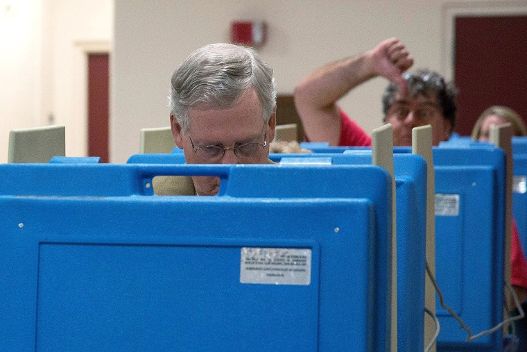 A voter gestures as Senate Minority Leader U.S. Sen. Mitch McConnell (R-KY) votes in the midterm elections at Bellarmine University on Nov. 4, 2014 in Louisville, Ky.