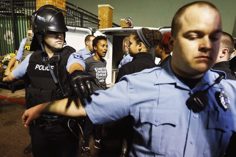 Police set up a perimeter around a protester who is detained during a demonstration at a Walmart store in St. Louis, Mo. on Oct. 13, 2014.