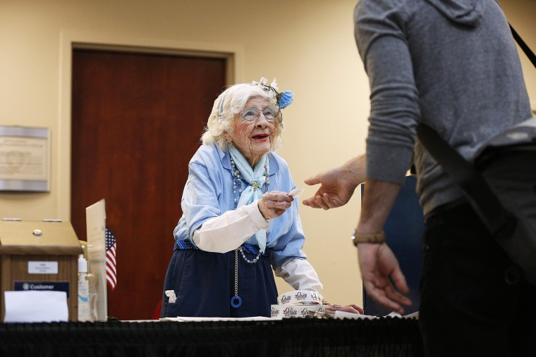 "Elections judge Constance Rolon, 96, of Denver, Colorado hands out ""I Voted!"" stickers as voters cast their ballots at the Denver Elections Division Building on Nov. 4, 2014."