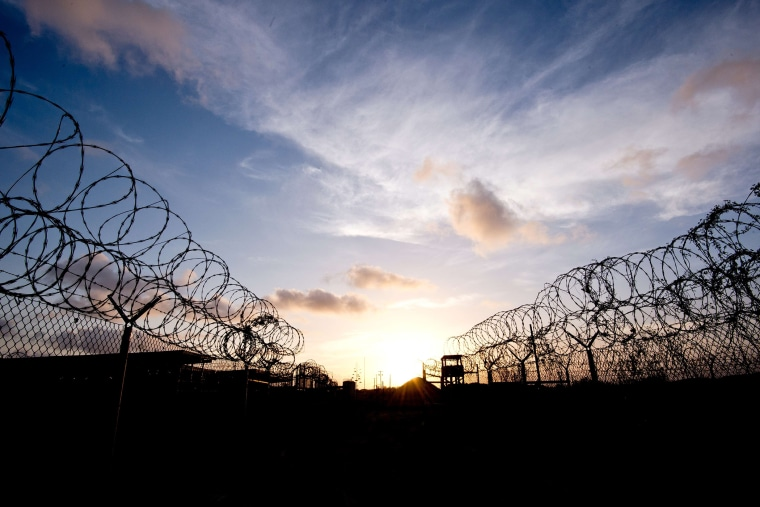 """This April 9, 2014 file photo made during an escorted visit and reviewed by the US military, shows the razor wire-topped fence and a watch tower at the abandoned \""""Camp X-Ray\"""" detention facility at the US Naval Station in Guantanamo Bay, Cuba."""