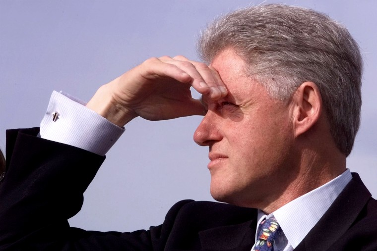 U.S. President Bill Clinton shades his eyes as he waits to be introduced at an event in Newport, R.I. in 1998.