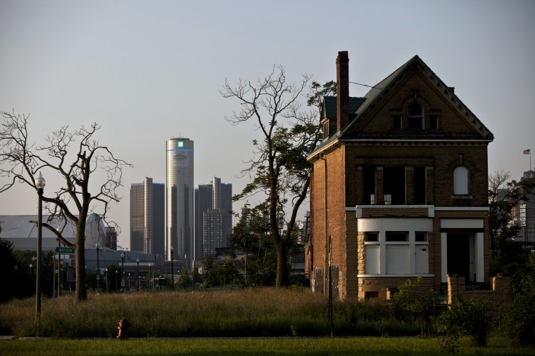 Early morning light falls on an a vacant, boarded up house as downtown Detroit is seen in the background, a day after the city filed for bankruptcy protection in court, in Detroit, on July 19, 2013.