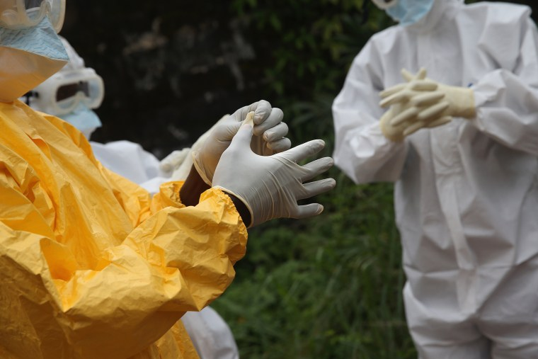 Health workers dress in protective clothing at the Island Clinic Ebola treatment center on Oct. 13, 2014 in Monrovia, Liberia. (John Moore/Getty)