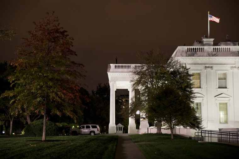 A group of Secret Service police gather on the North Lawn as a member of the Secret Service Counter Assault team surveys from the White House rooftop, Oct. 22, 2014, in Washington, D.C. (Photo by Jacquelyn Martin/AP)