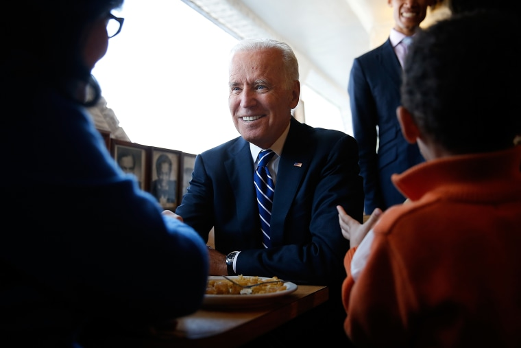 U.S. Vice President Joe Biden sits with customers while visiting a restaurant on March 26, 2014 in Washington, DC.
