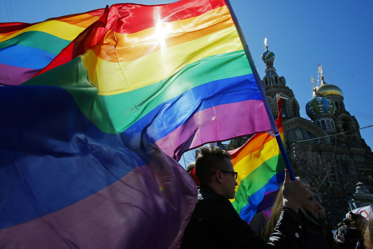 In this Wednesday, May 1, 2013, file photo, gay rights activists carry rainbow flags as they march during a May Day rally in St. Petersburg, Russia. (Photo by Dmitry Lovetsky/AP)
