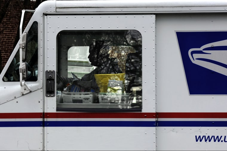 Postal carrier Anthony White sits in his truck while making his rounds in Kensington, Md. on Feb. 6, 2013.
