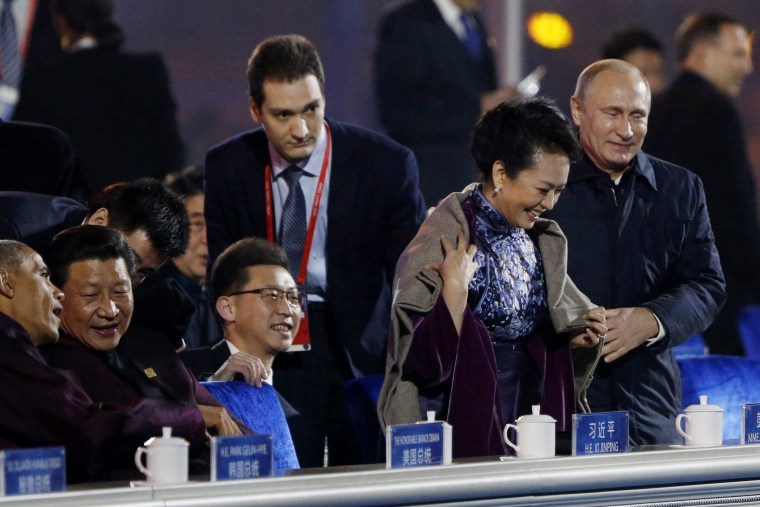 Russia's President Vladimir Putin (R) helps put a blanket on Peng Liyuan (2nd R), wife of China's President Xi Jinping (2nd L), as Xi talks to U.S. President Barack Obama (L) during a lights and fireworks show to celebrate Asia-Pacific Economic Cooperatio