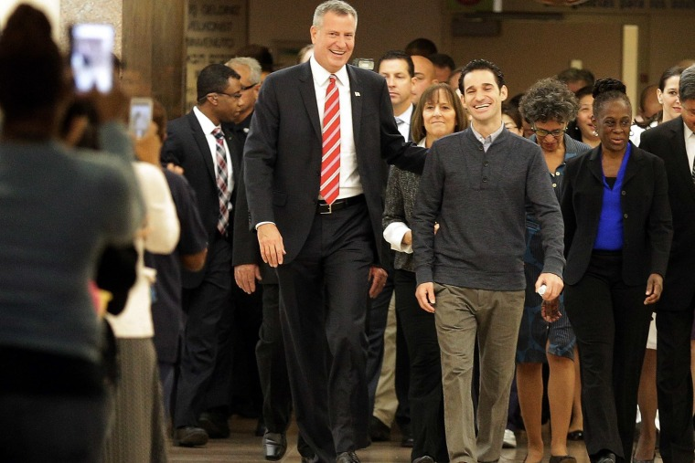 New York City Mayor Bill de Blasio (left) and his wife Chirlane McCray (right) flank Dr Craig Spencer (C) as Spencer leaves Bellevue Hospital after being declared free of the Ebola virus in New York, on Nov. 11, 2014.