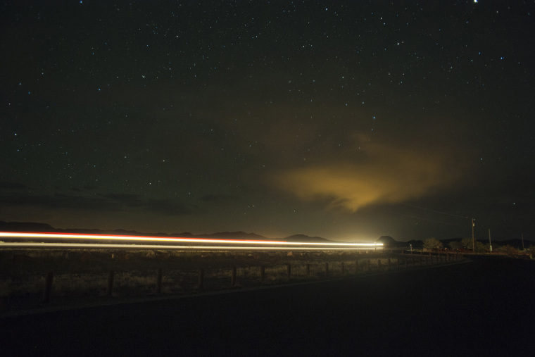 A car drives down the highway at night under a sky full of stars. (Photo by Justin Carrasquillo/Gallery Stock)
