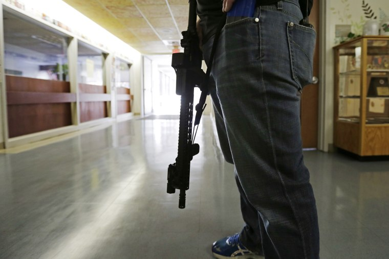 Lt. Greg Gallant, of the Methuen, Mass. police department, portrays an active shooter as he roams the halls of a school with an assault rifle, loaded with dummy rounds, during a demonstration in Methuen, Mass., on Nov. 11, 2014.