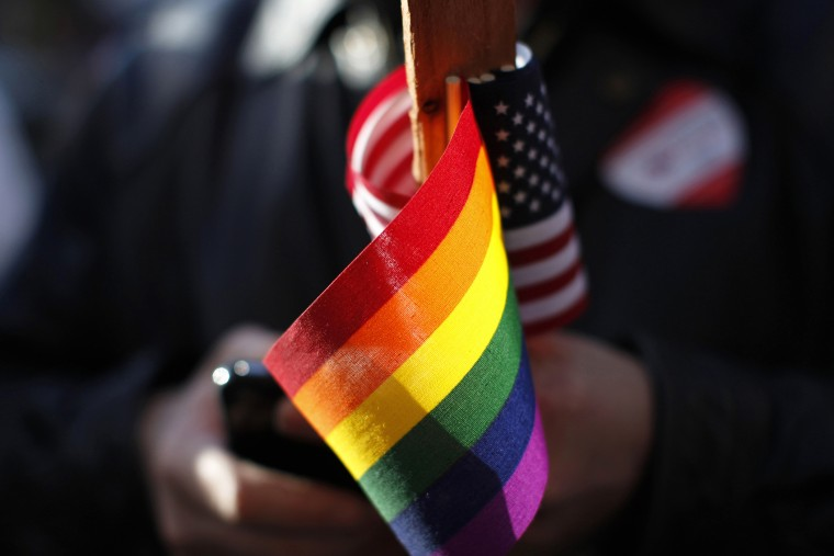 The gay pride and American flag are seen at a demonstration. (Photo by Stephen Lam/Reuters)