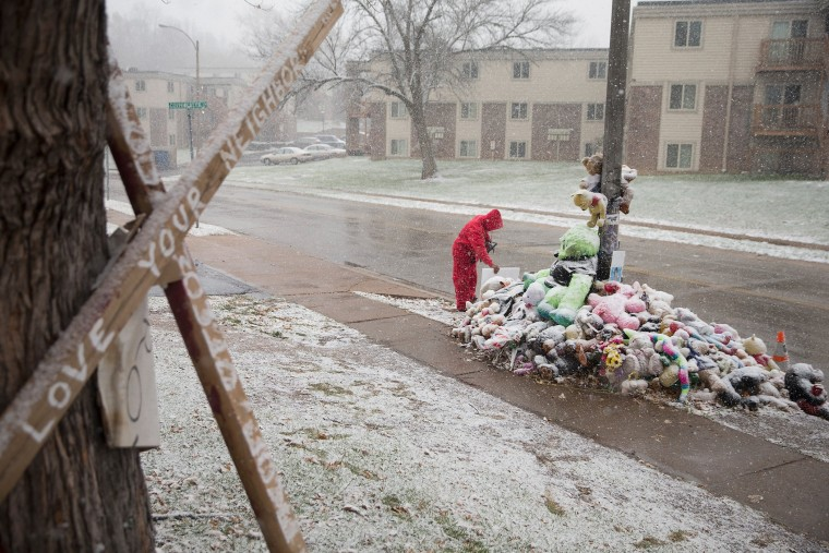 Chris Seltzer cleans the area around a memorial near the location where 18-year-old Michael Brown was shot, Nov. 16, 2014 in Ferguson, Mo. (Scott Olson/Getty)