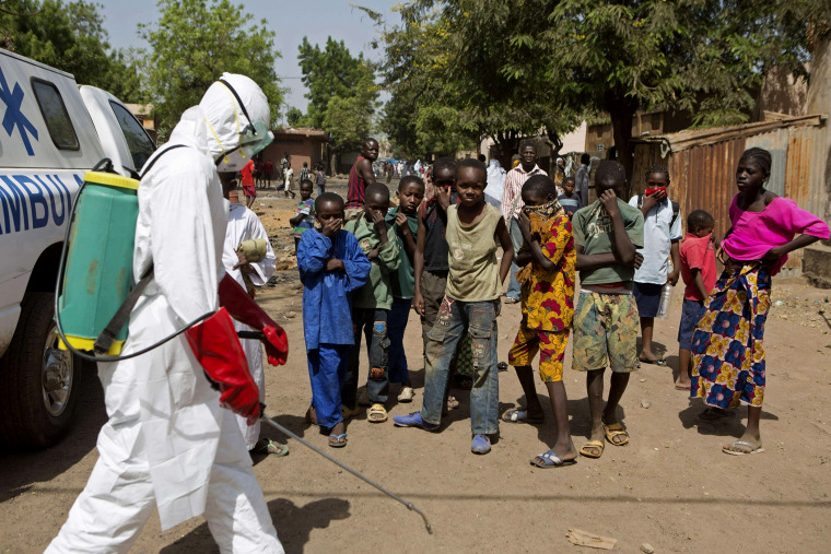Children watch as a health worker sprays disinfectants outside a mosque in Bamako, Mali on Nov. 14, 2014.