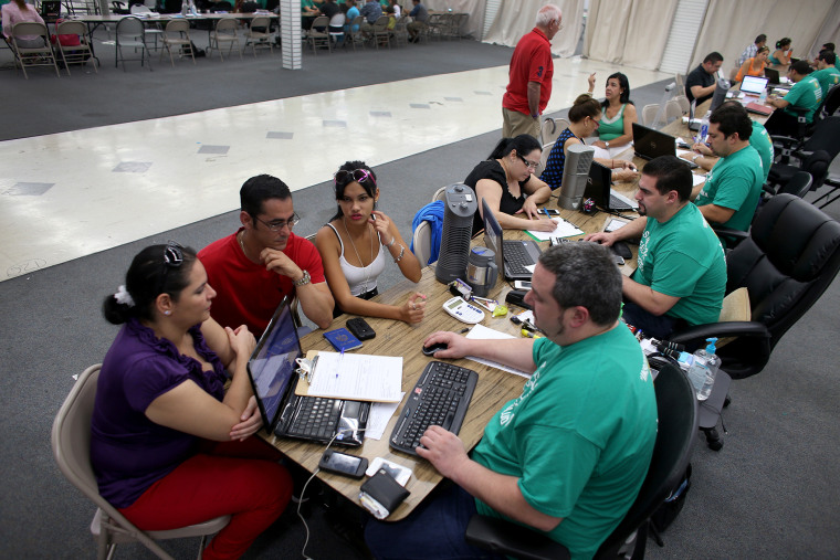 Yudelmy Cataneda, Javier Suarez and Claudia Suarez sit with Yosmay Valdivian, an insurance agent from Sunshine Life and Health Advisors, as they and others try to purchase health insurance under the Affordable Care Act at a store setup in the Mall of Amer