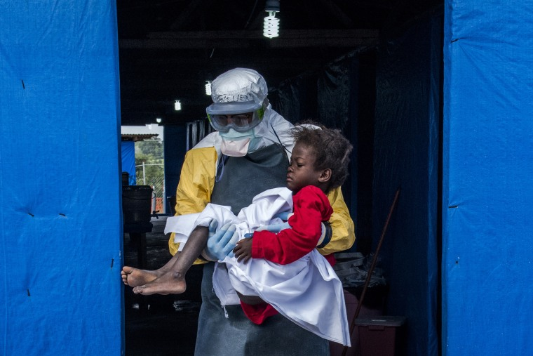 Dr. Steven Hatch carries Blessing Gea, 9, from the suspected ward to the confirmed high-risk ward after a blood test showed her positive for Ebola, at a clinic run by the International Medical Corps in the Suakoko of Liberia, Oct. 10, 2014.