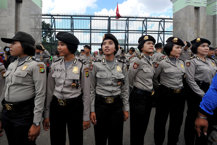 Indonesian policewomen stand guard while Indonesian workers of the All-Indonesia workers union (SPSI) hold a protest against the government's plan to hike fuel prices in Jakarta on March 29, 2012.
