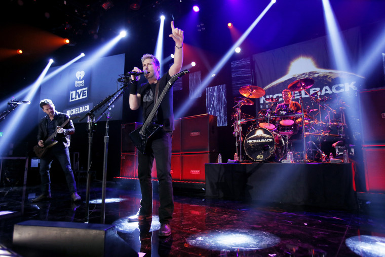 (L-R) Ryan Peak, Chad Kroeger and Daniel Adair from the band Nickelback perform at iHeartRadio Theater on Nov. 18, 2014 in Burbank, Calif. (Photo by Mike Windle/Getty for iHeartMedia)