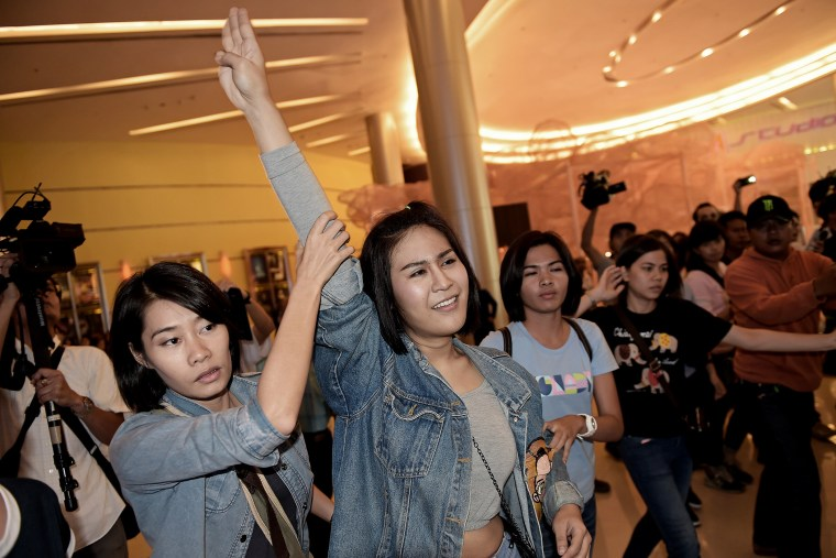 A Thai student flashes a three-finger salute as she is escorted out of a cinema hall by plainclothes female police officers in Bangkok on Nov. 20, 2014.