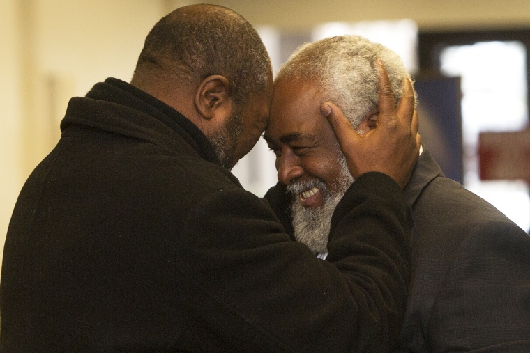 Wiley Bridgeman 60, right, of Cleveland, is greeted by his brother Ronnie, who is now known as Kwame Ajamu, after his release from a life sentence an hour earlier, by Cuyahoga County Common Pleas Judge David Matia, Nov. 21, 2014, in Cleveland.