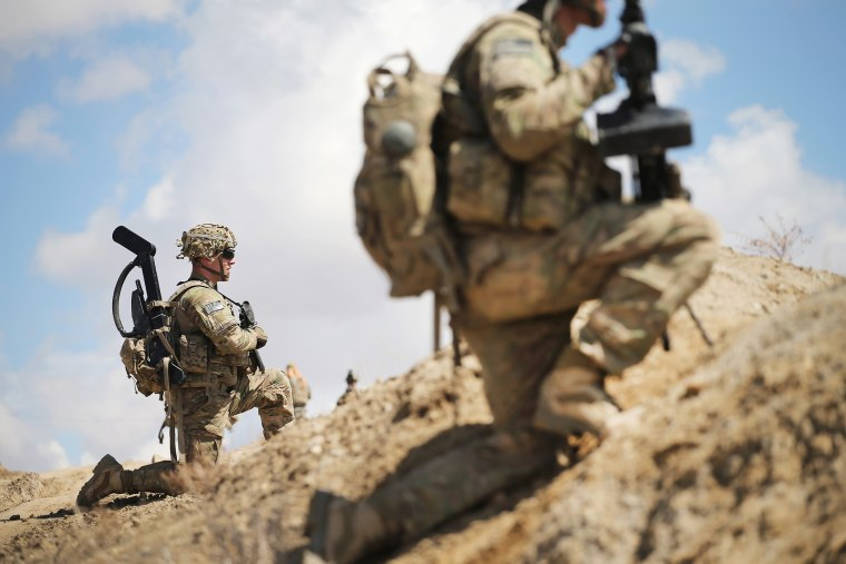 SGT Nathan Harrell (L) from Peru, New York with the U.S. Army's 2nd Battalion 87th Infantry Regiment, 3rd Brigade Combat Team, 10th Mountain Division patrols on the edge of a village on March 29, 2014 near Pul-e Alam, Afghanistan. (Scott Olson/Getty)