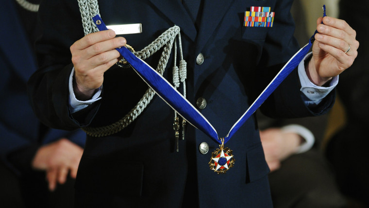 A military aide holds a medal during the Presidential Medal of Freedom ceremony at the White House on Nov. 20, 2013 in Washington, DC.