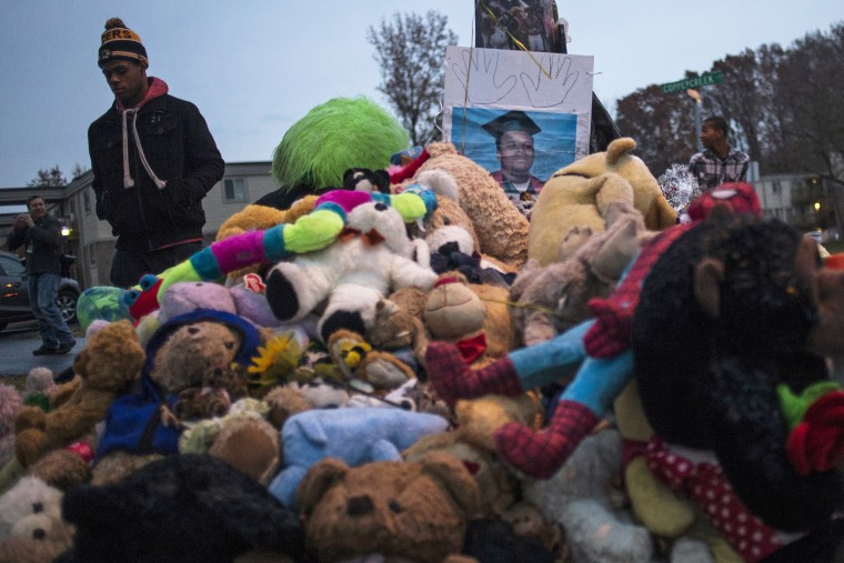 A resident walks past an image of 18-year-old Michael Brown placed at a makeshift memorial near the site where he was shot and killed in Ferguson, Mo. on Nov. 22, 2014. (Adrees Latif/Reuters)