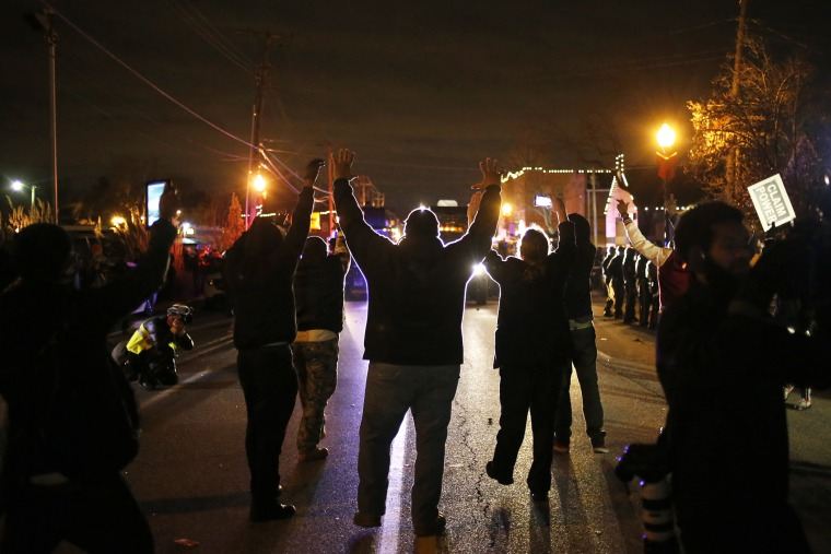 Protesters approach a police line with their hands up after a grand jury returned no indictment in the shooting of Michael Brown in Ferguson, Mo. on Nov. 24, 2014. (Photo by Adrees Latif/Reuters)