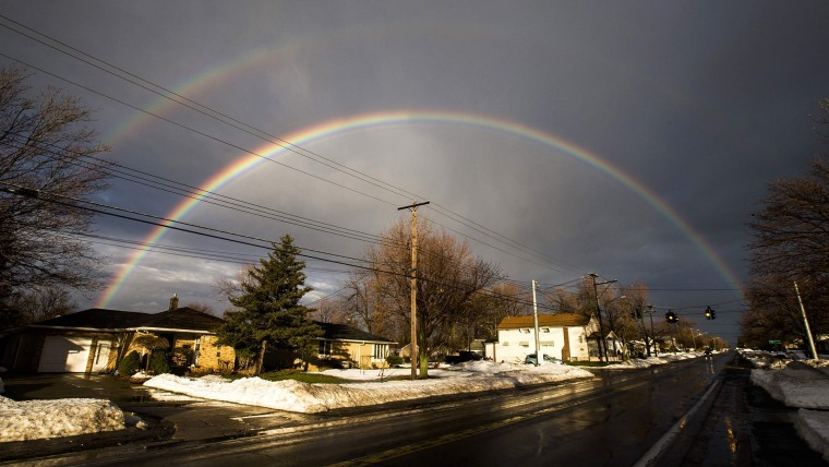 A rainbow forms over a neighbourhood following a massive snow storm in West Seneca, New York on Nov. 24, 2014