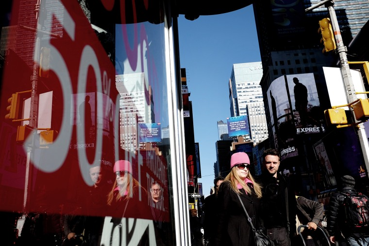 People walk past a store displaying a discount sign in Times Square in New York on Nov. 21, 2014. The National Retail Federation said last month it expects overall holiday sales this year to rise to $616.9 billion, a 4.1 percent increase from last year's