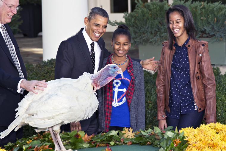 """President Barack Obama, with daughters Sasha, center, and Malia, right, carries on the """"presidential pardon"""" tradition at the White House in Washington, D.C., Nov. 21, 2012. (Photo by J. Scott Applewhite/AP)"""