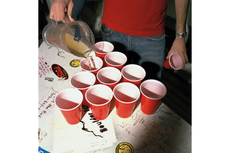 A college student fills cups of beer. (Photo by Brian Finke/Gallery Stock)