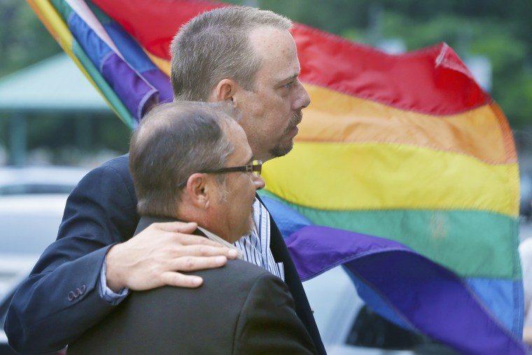 In this photo taken May 12, 2014, Shon DeArmon, top, and his partner James Porter carry a flag in support of the county issuing marriage licenses for same-sex couples at the Pulaski County Courthouse in Little Rock, Ark. (Photo by Danny Johnston/AP)