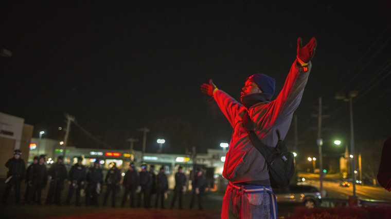 A protester gestures with his hands up in front of police officers during a second night of protests in Ferguson, Mo. on Nov. 25, 2014. (Photo by Lucas Jackson/Reuters)