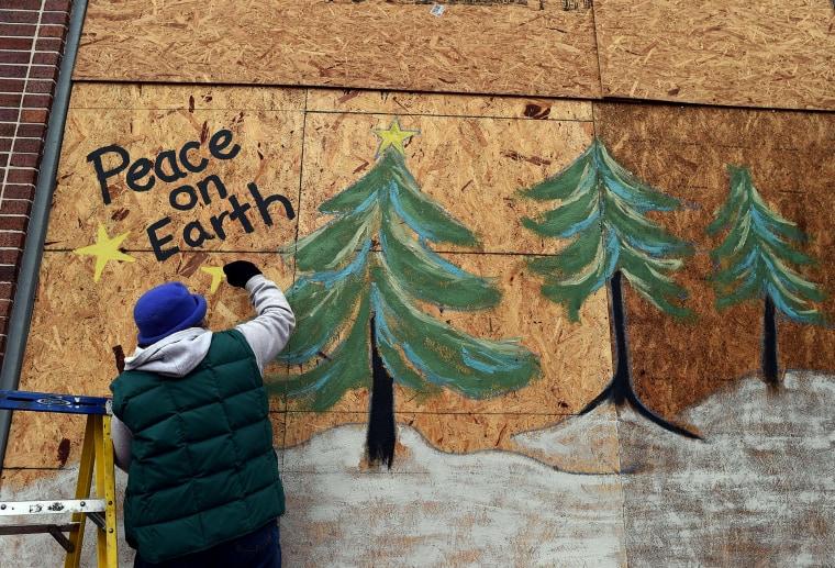 Karen Gold paints on a boarded window of her store in Ferguson, Missouri, on Nov. 26, 2014.