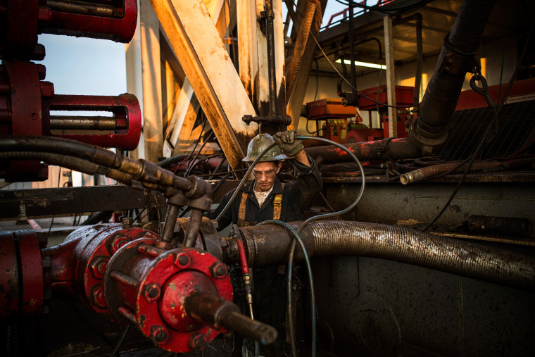 Ray Gerish, a floor hand for Raven Drilling, works on an oil rig drilling into the Bakken shale formation on July 28, 2013 outside Watford City, North Dakota. (Photo by Andrew Burton/Getty)