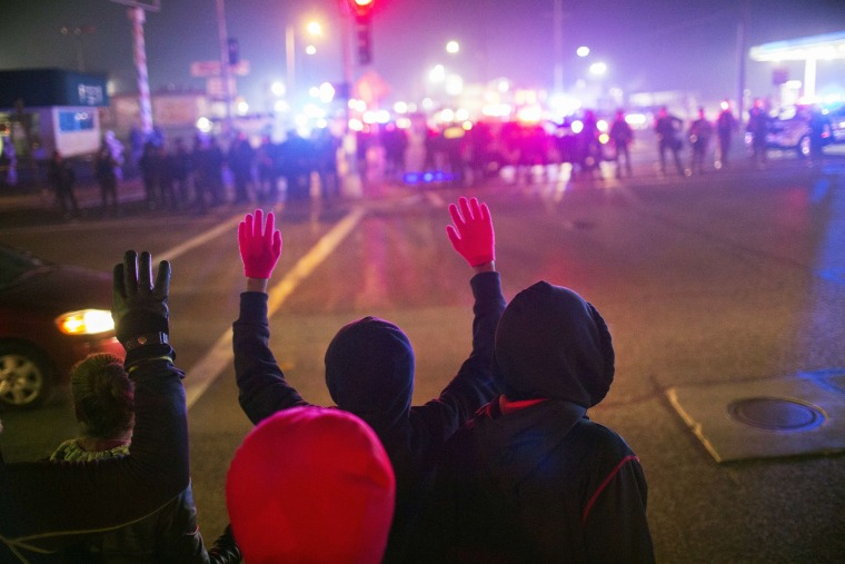 Protesters confront police officers during a second night of rioting in Ferguson, Mo. on Nov. 25, 2014. (Photo by Lucas Jackson/Reuters)
